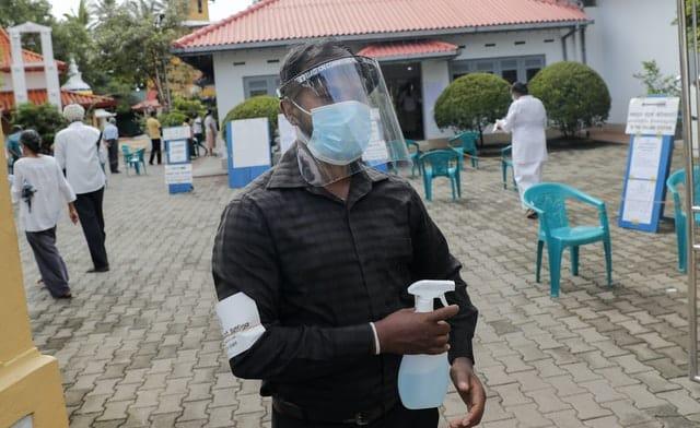 A Sri Lankan polling officer wearing mask and face shield stands holding a sanitiser sprayer (Eranga Jayawardena/AP)